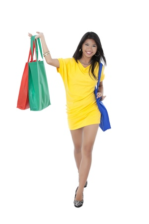 Portrait of a lady wearing a yellow dress smiling while holding shopping bags Stock Photo