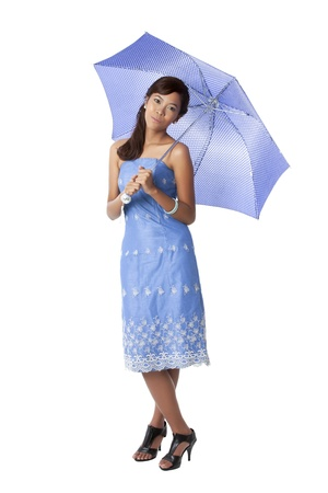 Portrait of a lovely lady in a dress holding a blue umbrella while standing on a white background Stock Photo
