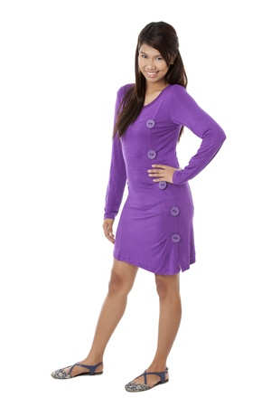 Portrait of a smiling lady wearing a purple dress and hands on hip against the white background