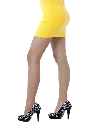 A young woman wearing yellow dress and black stiletto focusing her legs photo