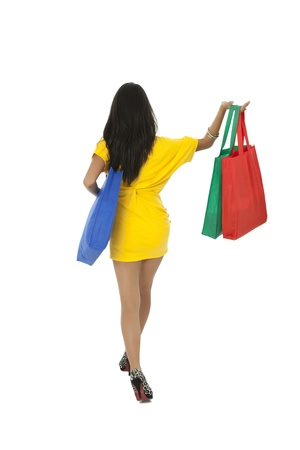 Back view image of a lady in a yellow dress with shopping bags Stock Photo - 17391660