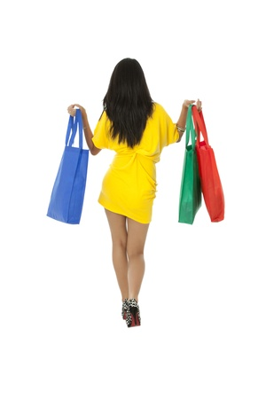 Back view of a gorgeous female walking in a white background with shopping bags Stock Photo - 17391661