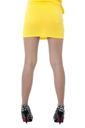 Back view image of a lady in yellow dress focusing her legs against the white background photo