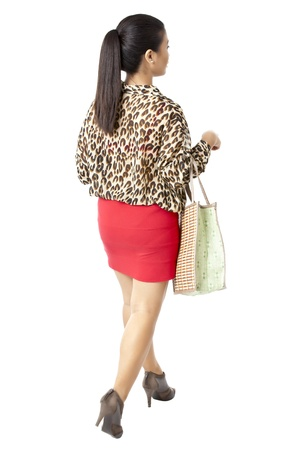 pinay: Back view image of a woman walking with a bag on a white background Stock Photo