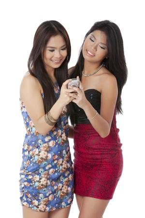 filipino ethnicity: Beautiful asian women reading message on a cellular phone