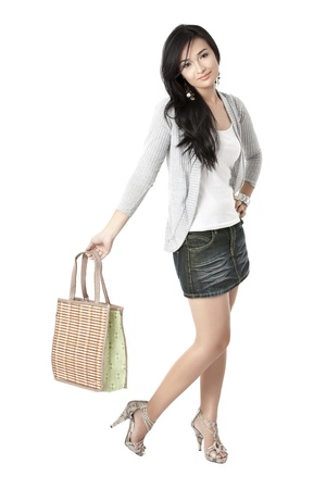 pinay: Portrait of beautiful girl holding a bag against white background Stock Photo