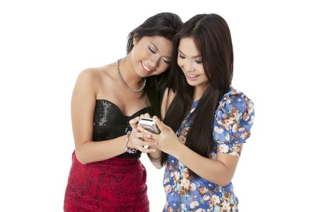 Portrait of beautiful ladies smiling while looking to the mobile phone against white background Stock Photo