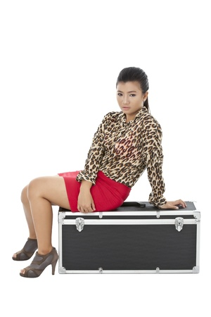 Portrait of a beautiful lady sitting on the luggage lying on the floor
