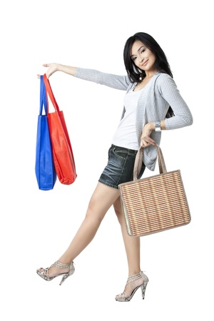 Beautiful posing of a female model holding trendy and shopping bags