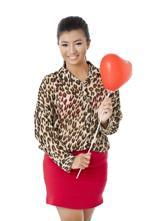 Portrait of charming teenage girl holding a red heart shape balloon against white background