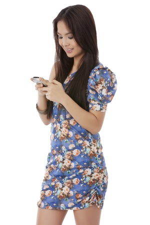 woman on phone: Cute Asian girl smiling while using her cellphone over a white background