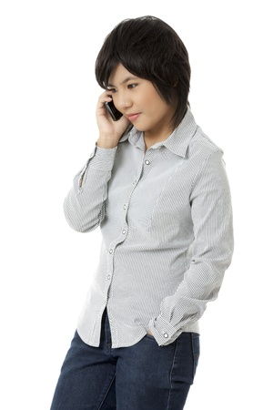 Side view of a cute Asian female talking on mobile phone against white background. Model: Leajzerlyn May R. Dion photo
