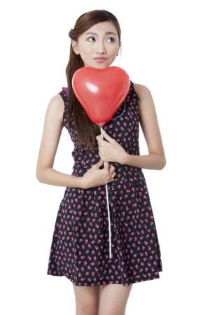 Portrait of a dreamy young girl holding a heart shape balloon over white background photo