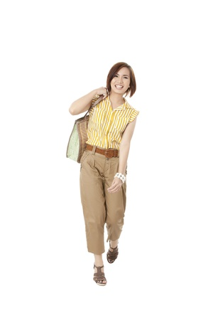 An image of a Filipino Woman carrying her bag and smiling while shes walking Stock Photo