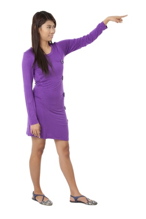 A standing Filipino woman pointing her finger on the side while smiling against white background Reklamní fotografie