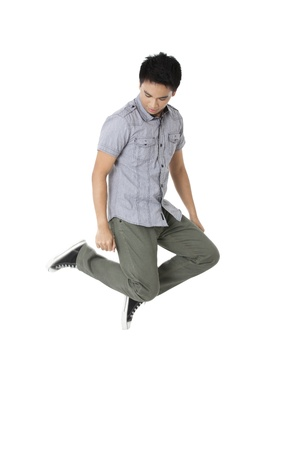 knees bent: Portrait of a young male with two knees bent floating in a white background Stock Photo
