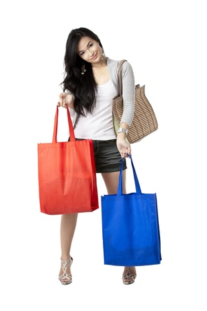 Facade shot of a gorgeous young female with bag on her shoulder and holding two more  shopping bags on her hands over white background