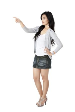 Élégant jeune femme pointant sur fond blanc