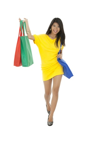 Portrait of happy beautiful lady carrying shopping bags against white background photo