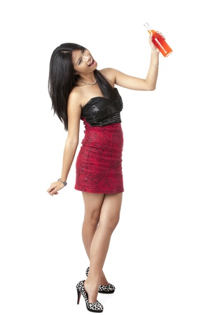 pinay: Happy beautiful lady raising a bottle of drink against white background Stock Photo