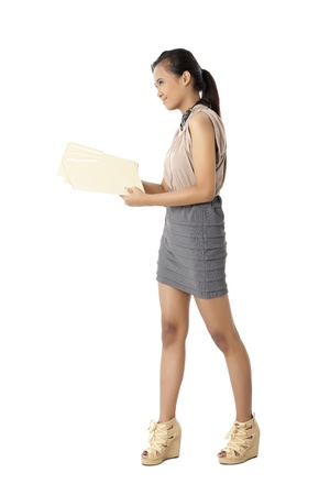 pinay: Portrait of office girl smiling while holding documents against white background Stock Photo