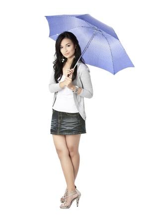 Portrait of a pretty Asian holding a purple umbrella against white background photo