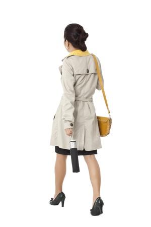 um jovem mulher só: Vista traseira de um andar novo asi�tico f�mea atrativa com guarda-chuva e bolsa para transporte contra um fundo branco. Modelo: Novaliza T. Garcia Imagens