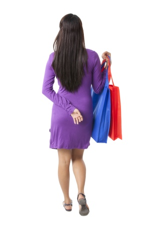 pinay: Rear view image of a woman wearing a purple dress with shopping bags walking on a white background