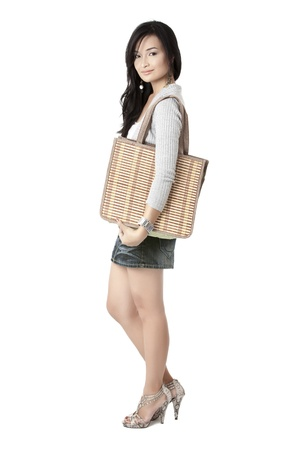 Portrait and side view image of pretty Asian model but still facing on camera with her stylish bag photo