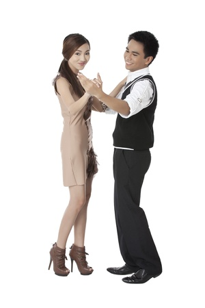Portrait of young couple dancing against white background photo