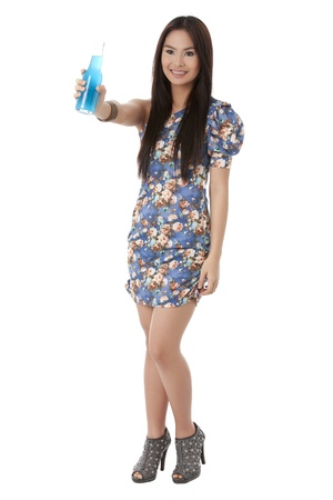Portrait of a young female standing in a white background raising a bottle with blue content photo