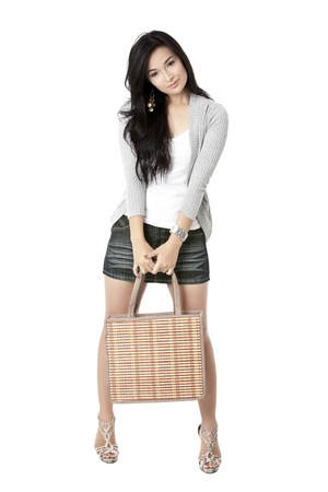pinay: Portrait of a beautiful young woman holding a bag while posing on a white background