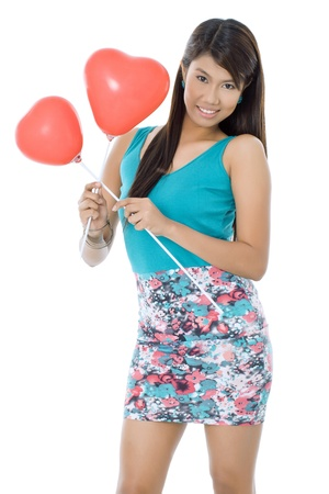 Female Asian model smiling while holding two heart shape balloons  isolated in a white background photo