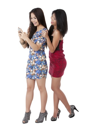 Portrait of happy ladies looking on the cellphone over the white background photo