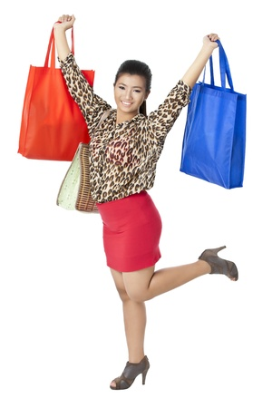 Portrait of a happy woman with her shopping bags against white background photo