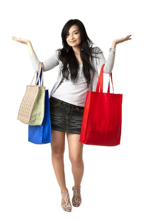 Portrait o a beautiful young woman holding shopping bags on white background photo