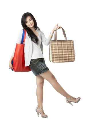 Portrait of a lovely lady holding shopping bags while swaying her feet Stock Photo - 17422520