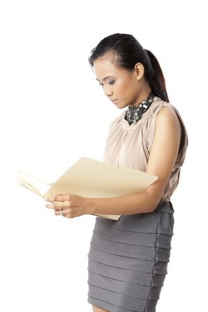 pinay: Portrait of office girl holding and looking a folder against whiten background