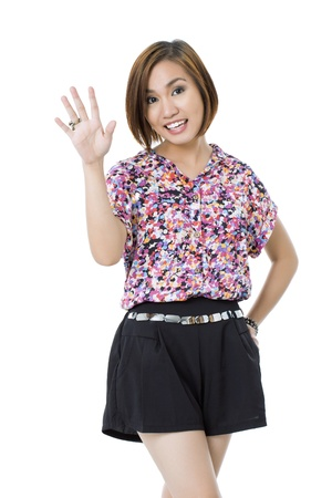 pinay: Portrait of a pretty woman waving her hand while smiling at the camera isolated in a white background Stock Photo