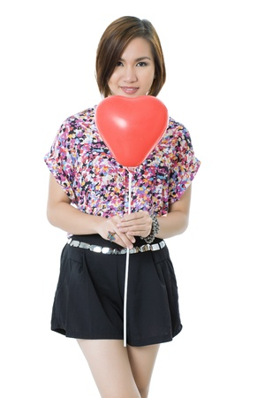 Portrait of a pretty woman in a white background, holding a red heart shape balloon on her front as she smiles for the camera