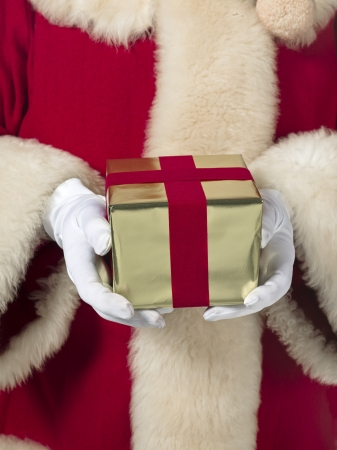 Santa Claus holding a gift box in a macro image photo