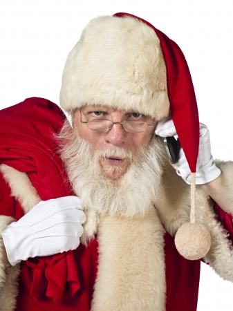 A close up portrait of Santa while holding a cellular phone and a sack of gift looking straight at the camera photo