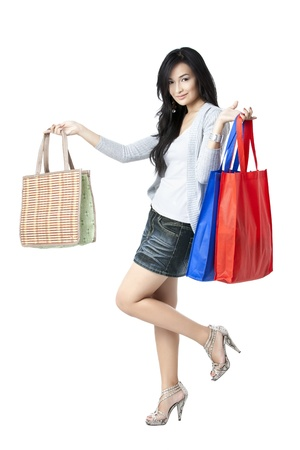 Portrait of a sexy and pretty Asian with her shopping bags on her satisfying and happy look photo