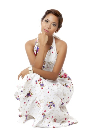 pinay: Sitting young female with her hand on her chin and slightly pouting her lips over a white background Stock Photo