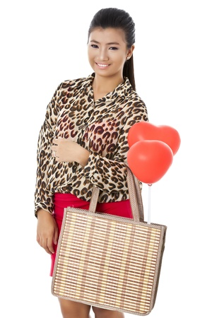 pinay: Portrait of a smiling beautiful lady holding bag and balloons against the white surface
