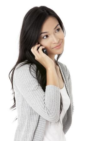 彼女の携帯電話を使用した呼び出しが白い背景で分離しながら笑みを浮かべて女性のショットで引けた