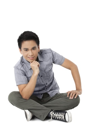 pinoy: Portrait of teenager guy sitting on the floor against white background