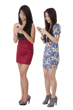 pinay: Image of two beautiful young ladies holding their cellphone and texting