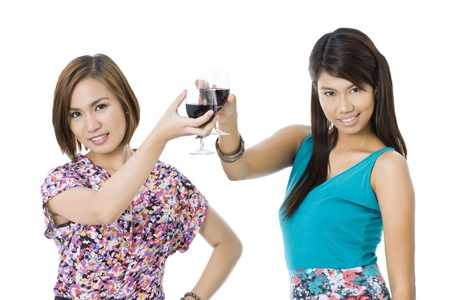 Two female Asian model doing cheers with wine glasses isolated in a white background