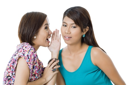 pinay: Portrait of two girls talking against white background Stock Photo
